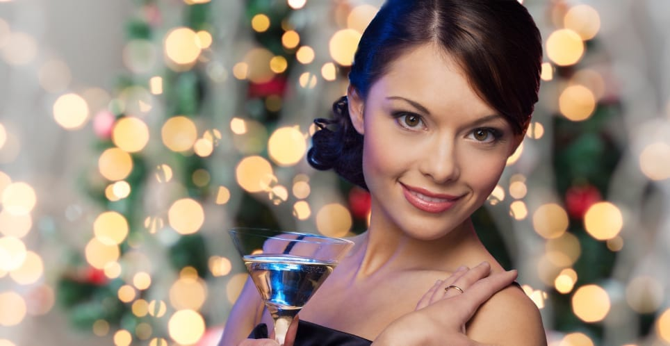 woman face with cocktail over christmas lights