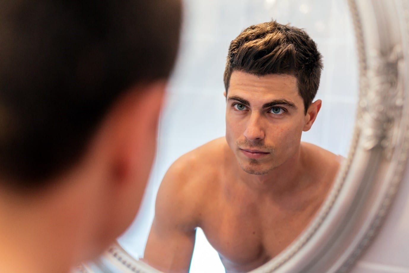 aesthetic treatments for men - man looking in the mirror